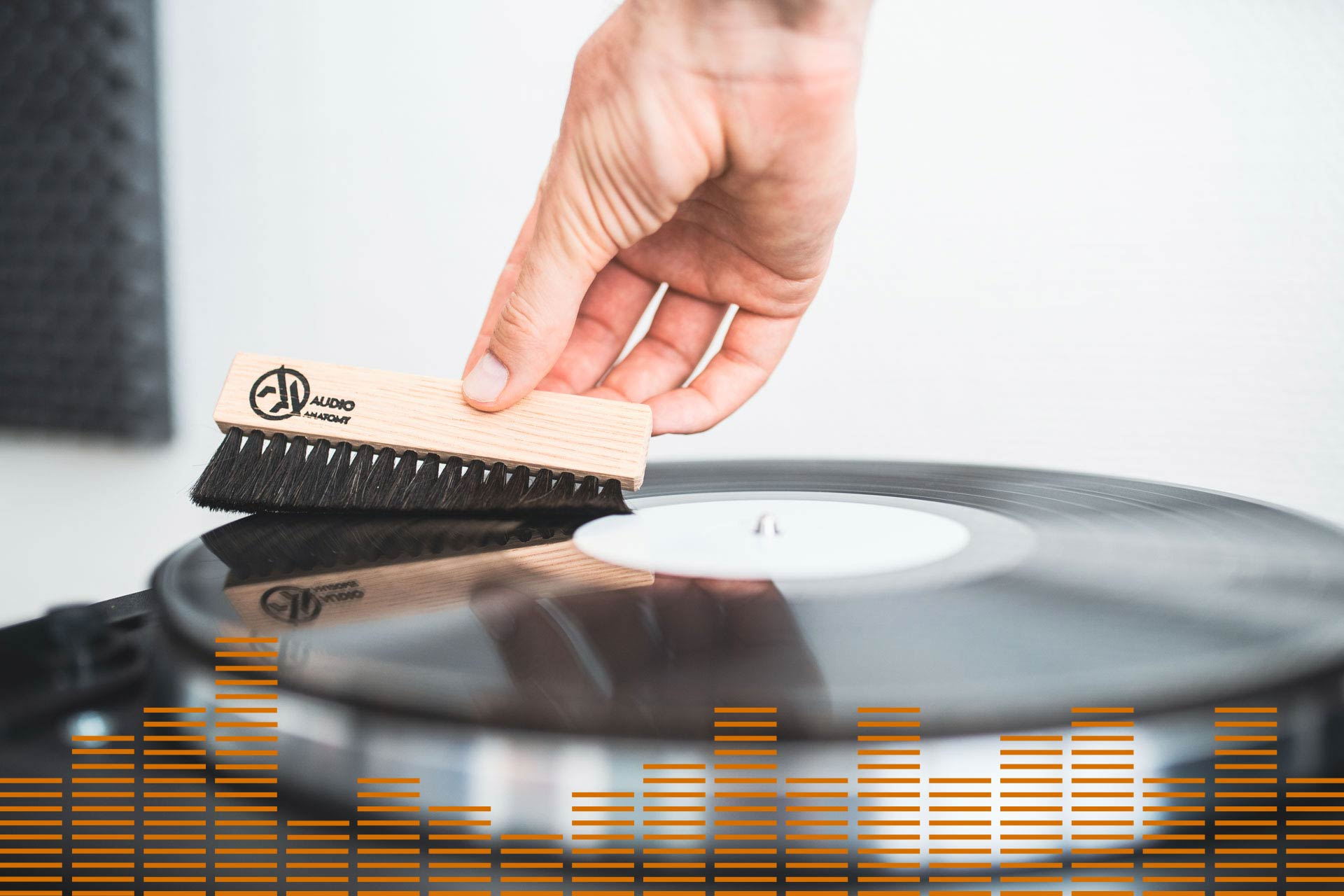 A person cleans a LP with a brush